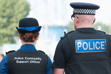 A female PCSO and a male police officer walking away from the camera