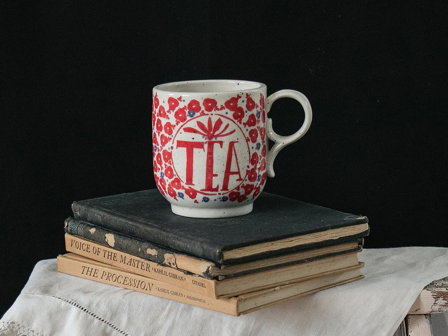 Pretty tea cup on top of a pile of old books